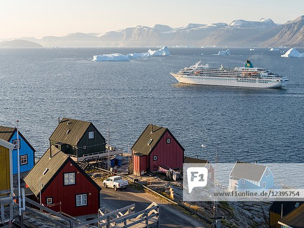 Small town Uummannaq in the north of west greenland. Background cruise ship and the glaciated Nuussuaq (Nugssuaq) Peninsula. America  North America  Greenland  Denmark.