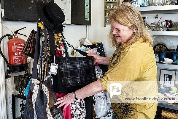 Tilburg  Netherlands. Mature adult  female shop owner rearanging a supply of handcrafted ladies bags.