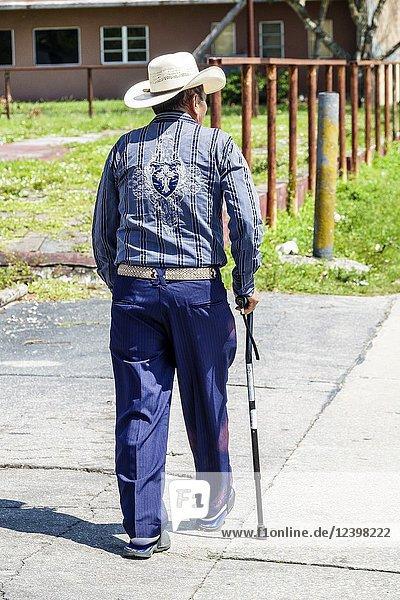 Florida  Immokalee  agricultural town  Hispanic  senior  man  walking cane  cowboy hat  Western attire
