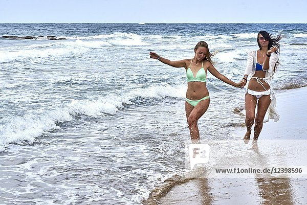 Two young women running at beach in bikini  holding hands. Malia  Crete  Greece.