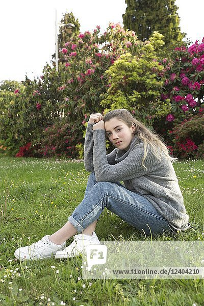 16 year old teenager sitting in a park with grass and flowers  taken in Limoges  France.