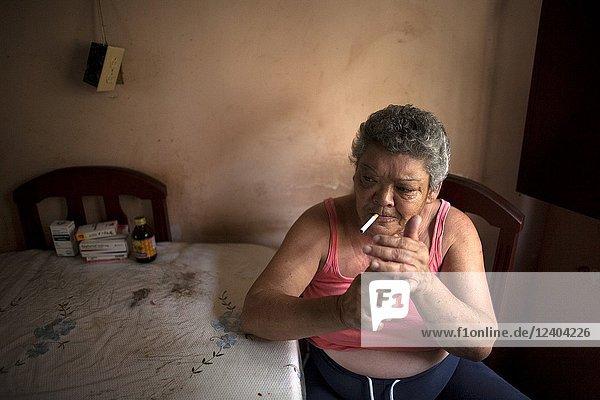 Emperatriz Santiago smokes a cigarette in her home in Los.
