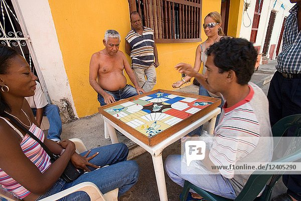 Neighbors of the Getsemani neighborhood playing parchis on a street next to their houses. Cartagena de Indias  Colombia.