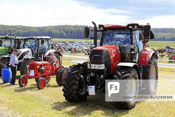 Big Case IH 165 and small Valmet 15 tractors  latter driven by young boy on Kimito Traktorkavalkad  Tractor Cavalcade. Kimito  Finland - July 7  2018.