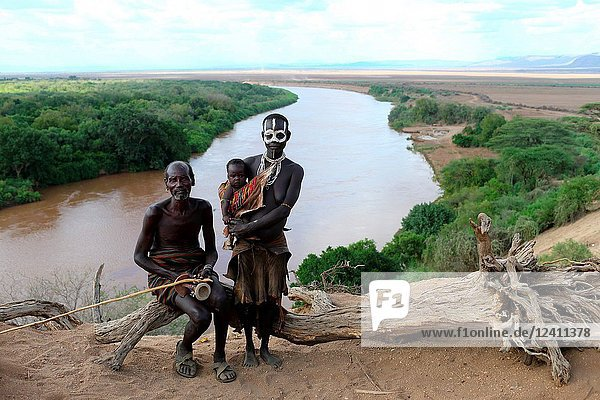 Group of people from Karo tribe with woman holding her baby in front of Omo river  Ethiopia  East Africa.