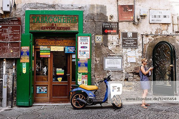 Woman and vespa motorbike next to local tobacco shop  Naples  Campania  Italy.