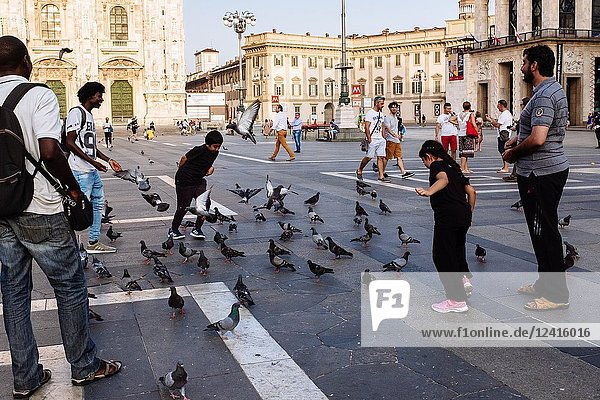 Tourists playing with pigeons in Piazza del Duomo square  Milan  Lombardy  Italy.