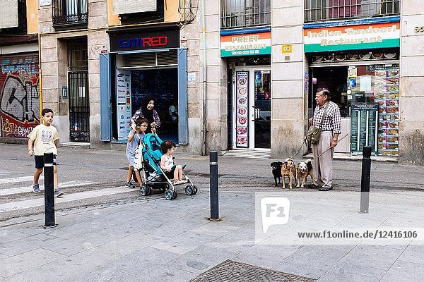 Muslim family walking down a street while local senior man with his dogs are standing in front of indian restaurant  in El Raval neighborhood  Barcelona  Catalonia  Spain.