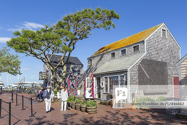 Tourists and visitors shop and stroll along Straight Wharf in Nantucket  Massachusetts.
