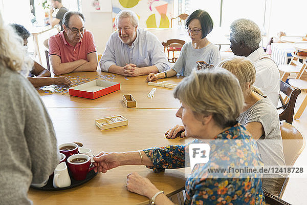 Senior friends playing games and drinking tea at table in community center
