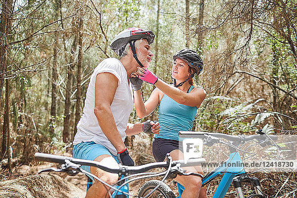 Daughter helping father with mountain biking helmet on trail in woods