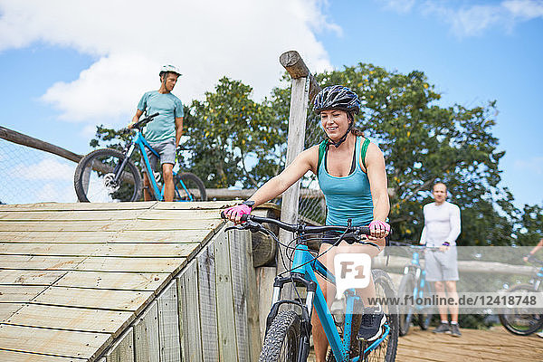 Smiling young woman mountain biking at obstacle course