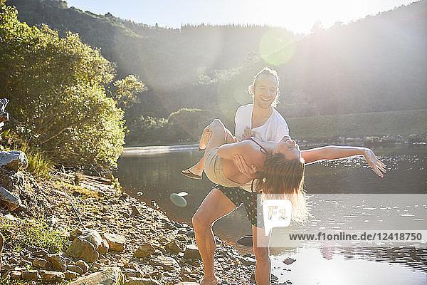 Playful couple at sunny summer lake