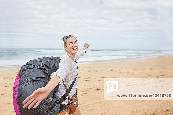 Portrait smiling  carefree young female paraglider with parachute backpack on ocean beach