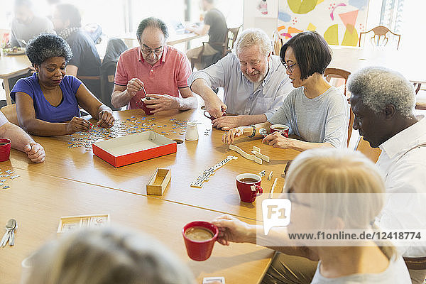 Senior friends playing games at table in community center