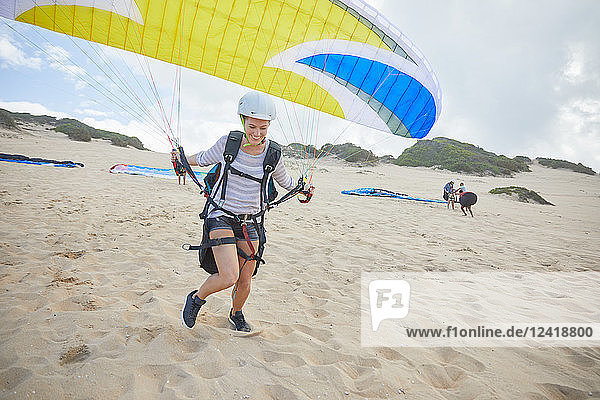 Female paraglider with parachute running  taking off on beach