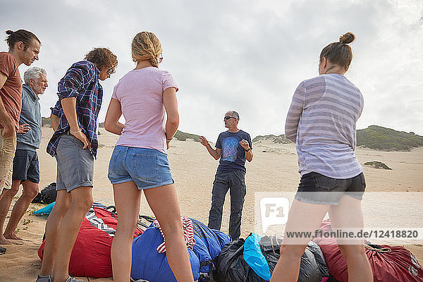 Male paragliding instructor talking to students on beach