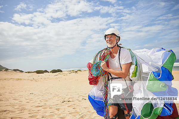 Smiling male paraglider carrying equipment and parachute on sunny beach