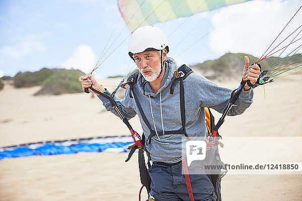 Focused mature male paraglider with equipment and parachute on beach