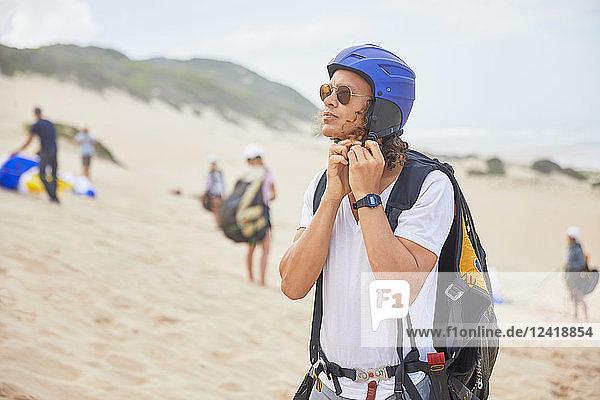 Male paraglider fastening helmet on beach