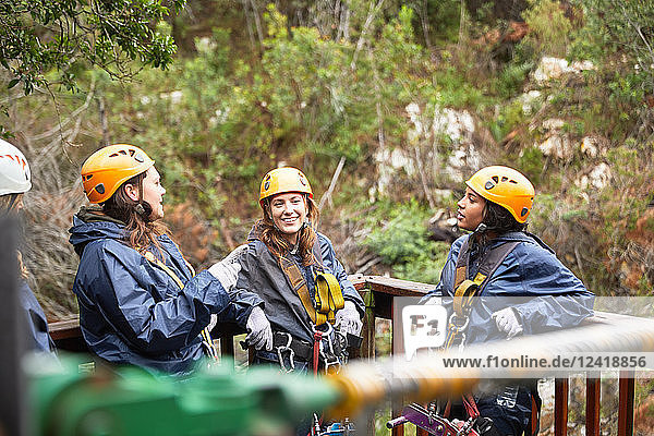 Smiling women friends talking  waiting to zip line