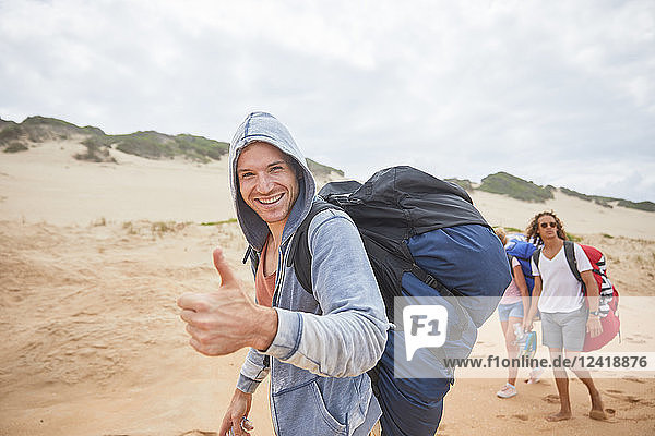 Portrait confident man with paragliding parachute backpack on beach