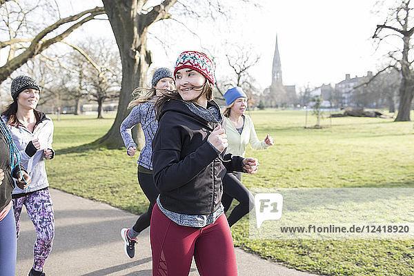 Confident female runner running in sunny park