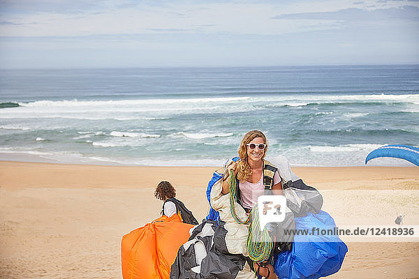 Portrait smiling  confident female paraglider with equipment on sunny ocean beach