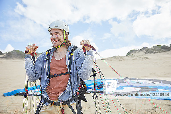 Smiling  confident paraglider with parachute on beach
