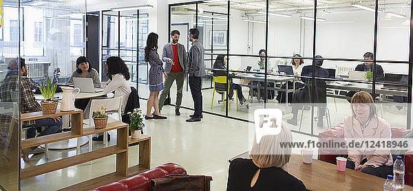 Creative business people talking in open plan office