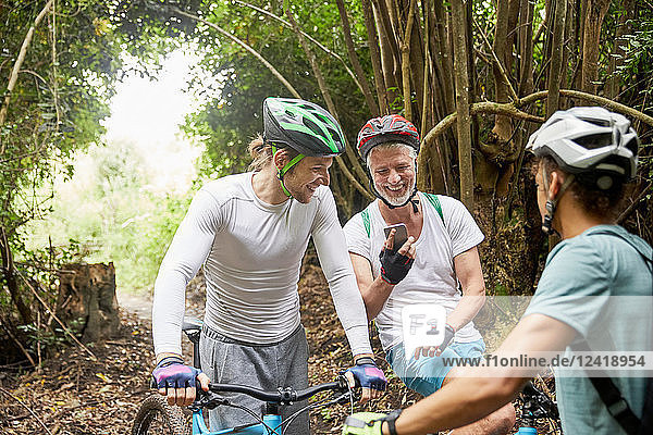 Male friends mountain biking  using smart phone in woods