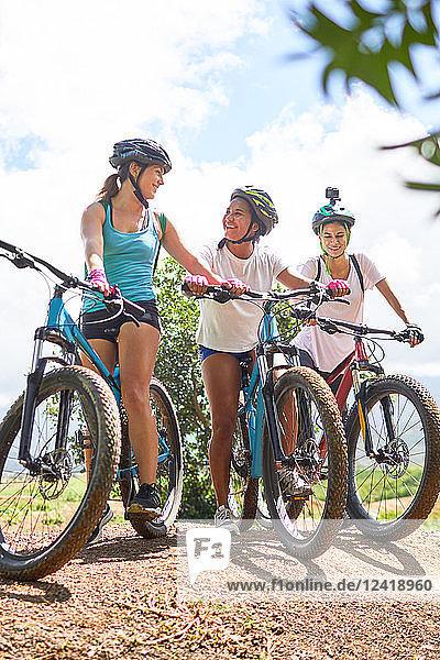 Women friends mountain biking on sunny trail