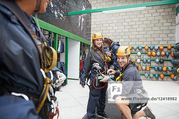 Portrait smiling couple preparing zip line equipment