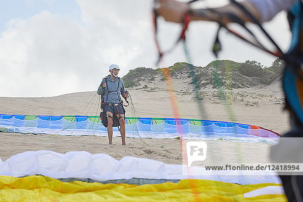 Male paraglider with parachute on beach