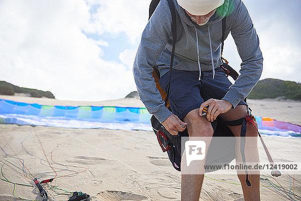 Male paraglider preparing equipment on beach