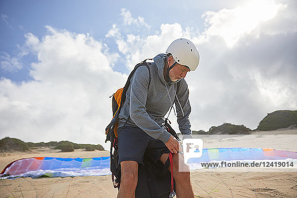 Male paraglider preparing on sunny beach