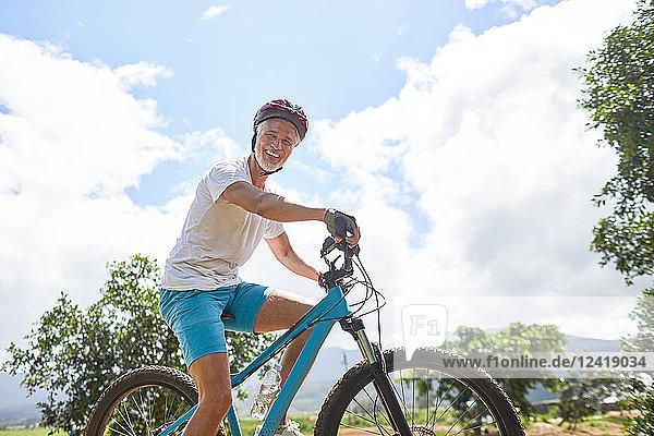 Portrait smiling  confident mature man mountain biking