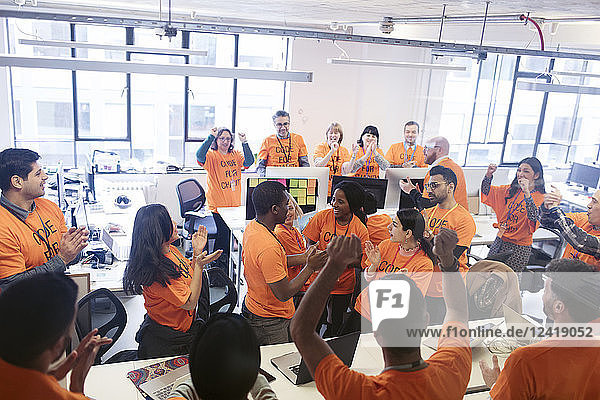 Hackers celebrating  coding for charity at hackathon