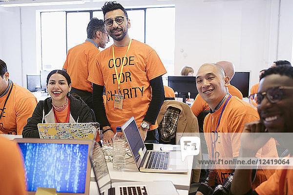 Portrait confident hackers coding for charity at hackathon