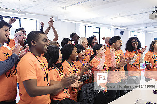 Happy hackers cheering and celebrating  coding for charity at hackathon