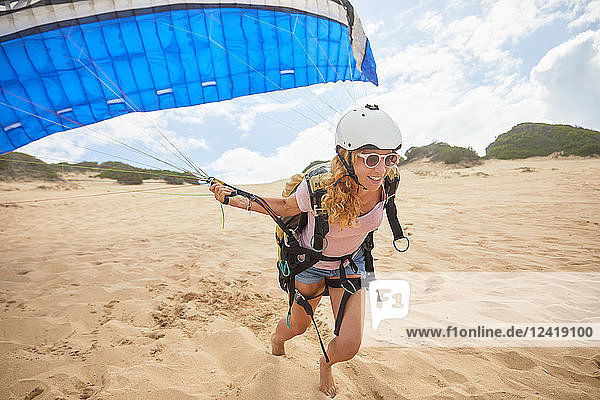Smiling female paraglider running with parachute on beach