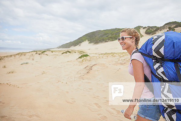 Smiling female paraglider with parachute backpack on beach