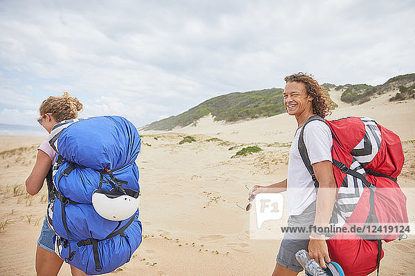 Portrait happy male paraglider with parachute backpack on beach