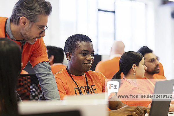 Hackers at laptops coding for charity at hackathon