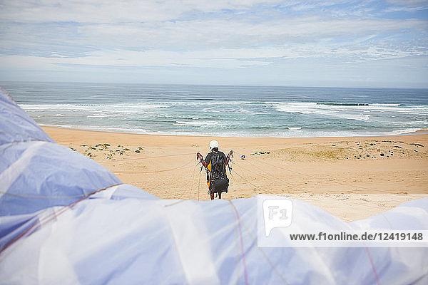 Paraglider with parachute on ocean beach
