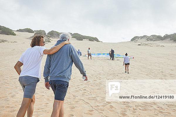 Paraglider friends walking on beach