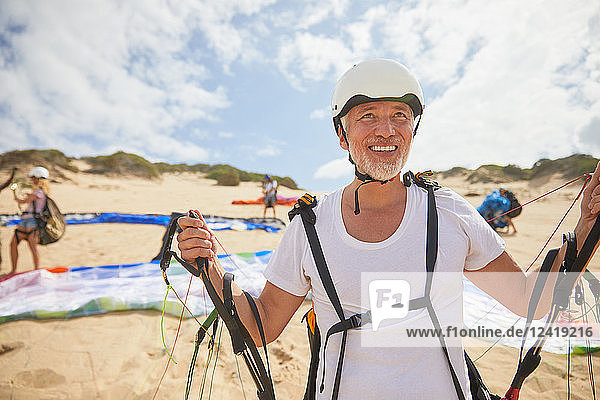Mature male paraglider on beach with equipment