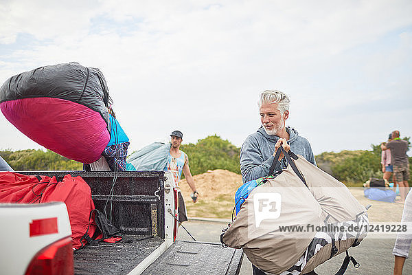 Mature male paraglider unloading parachute from truck