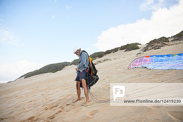 Male paraglider preparing equipment on beach