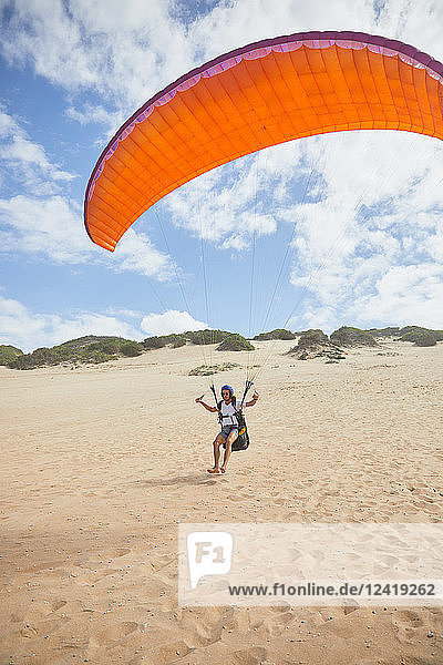Male paraglider running with parachute on beach